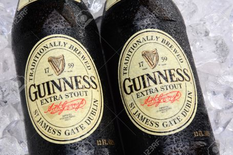 IRVINE, CA - MAY 25, 2014: Two bottles of Guinness Extra Stout on a bed of ice. The Irish beer is one of the worlds most successful beer brands with annual sales over 850 million liters.